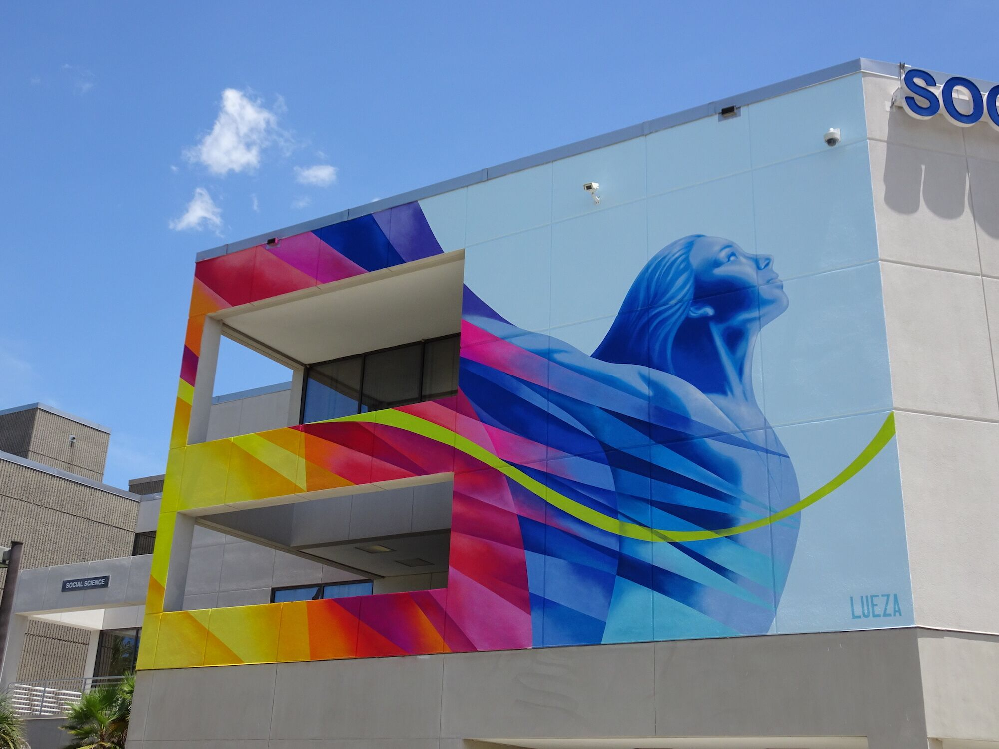 Colorful mural of a woman with arms lifted