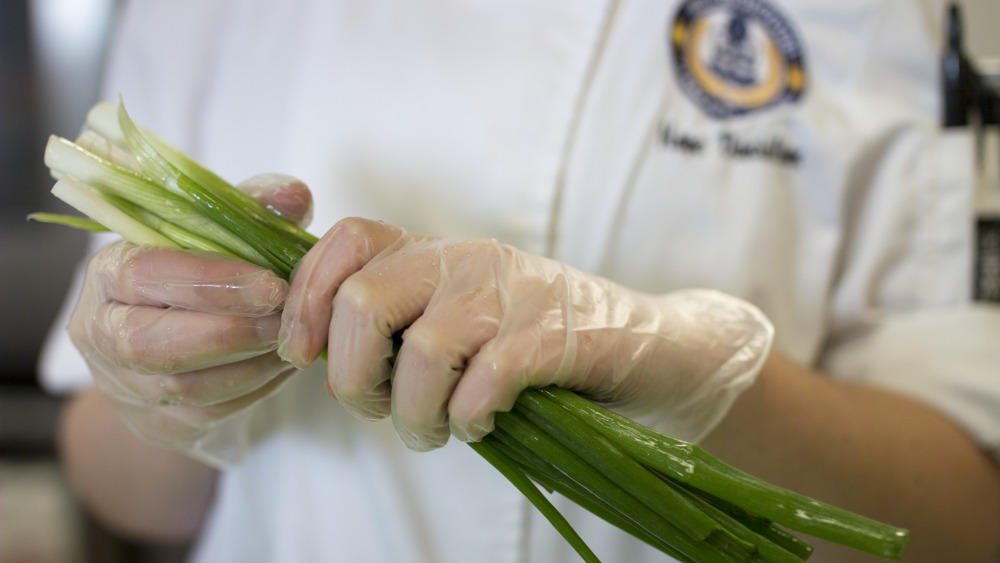 closeup of hands holding washed green onions, individual is wearing a chef's jacket with the HCC seal