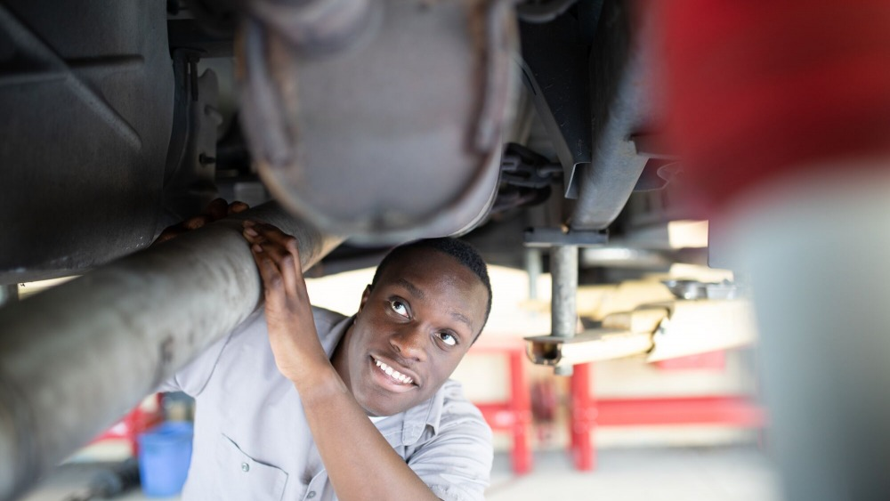 African American male auto tech student looking at a vehicle.