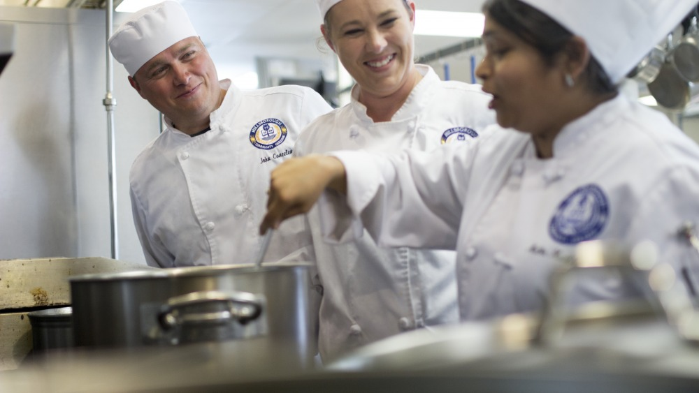 People wearing chef's jacket and hats, one individually is stirring the pot and speaking while the other two watch and smile