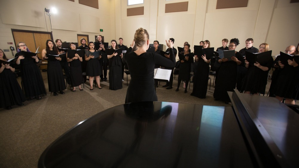 Backside of a choir conductor orchestrated a group of choir students, all wearing black