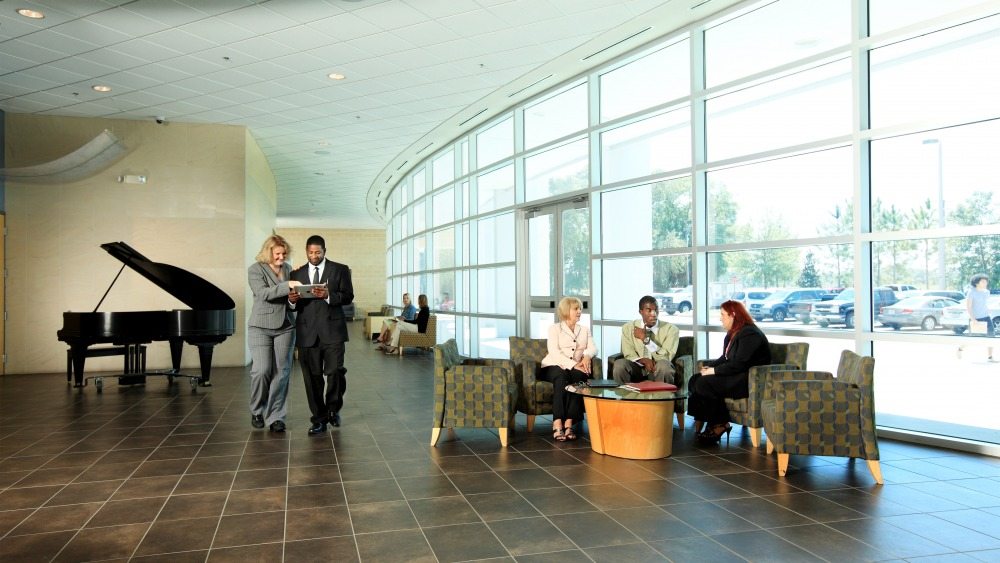 People dressed professionally speaking inside the lobby of the Trinkle Center