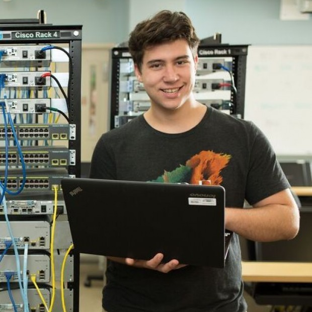 male student holding laptop next to computer servers.