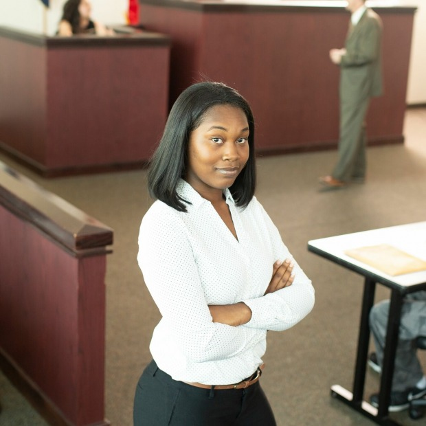 Paralegal student posing in front of courtroom