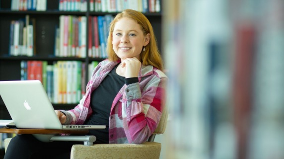 female student sitting inside library and smiling at the camera