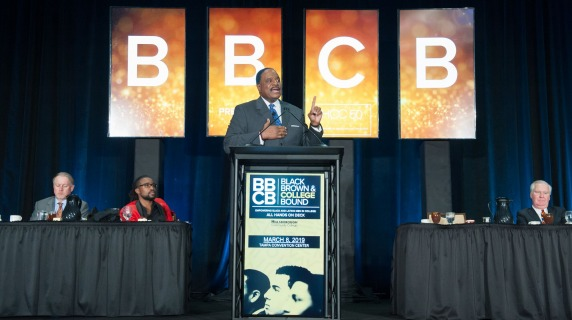 James Brown speaking at a podium on stage in front of BBCB displayed on digital monitors behind him