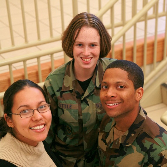 Two students in military uniform and one student in civilian attire on a staircase