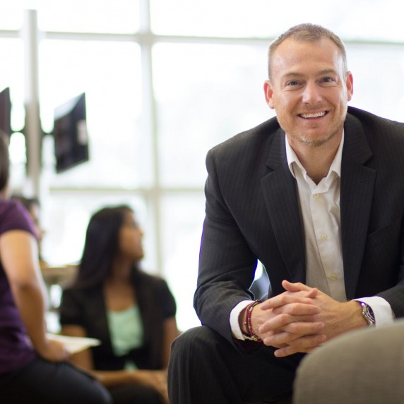 Smiling white adult male wearing a business suit sitting in a lounge leaning forward with students in the background