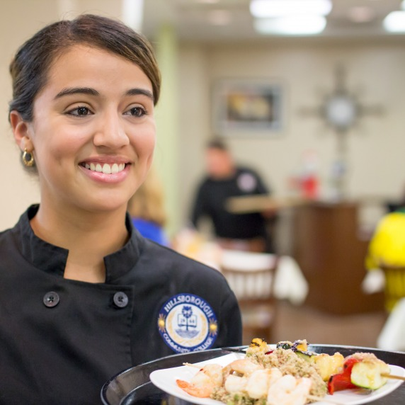 Smiling female hispanic student wearing a black chef's jacket, holding a tray of food in the Gourmet Room restaurant