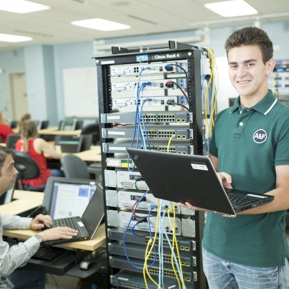 Smiling white male student holding a laptop standing next to a Cisco server rack in a classroom with other students