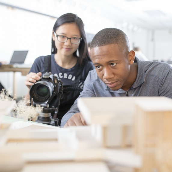 A young asian student holding a Canon camera on a tripod, next to a black male student who's looking at architectural models