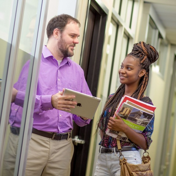 male Advisor and female student conversing in a hallway