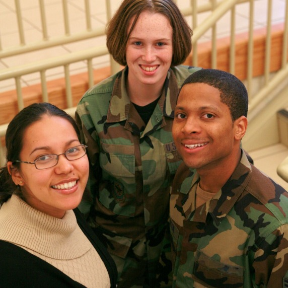 Two students in uniform and one student in civilian attire standing on a stairwell