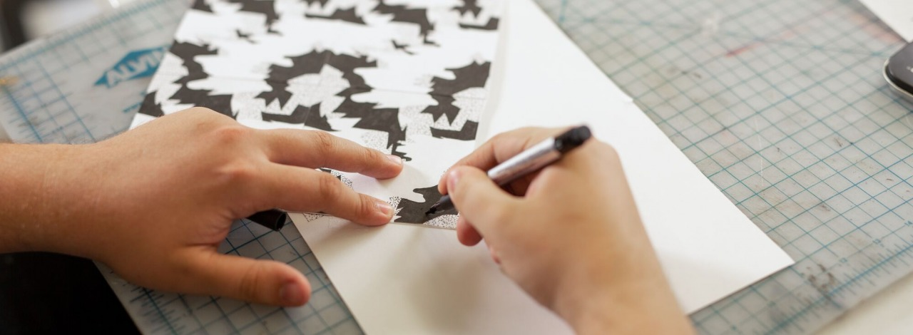 close-up of hands drawing a tessellation on paper pressed on a self-healing cutting mat