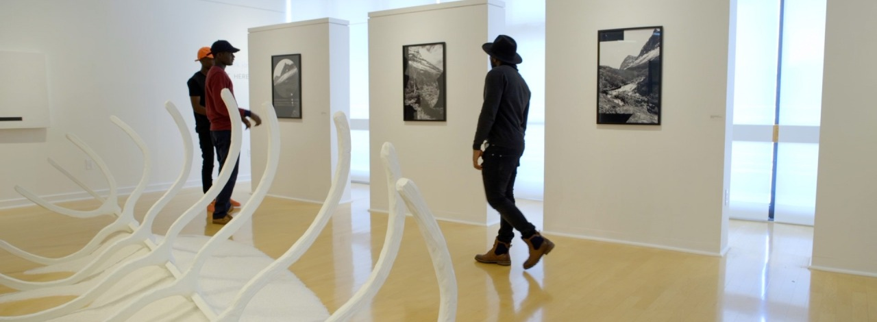 African American males walking through and enjoying an art gallery