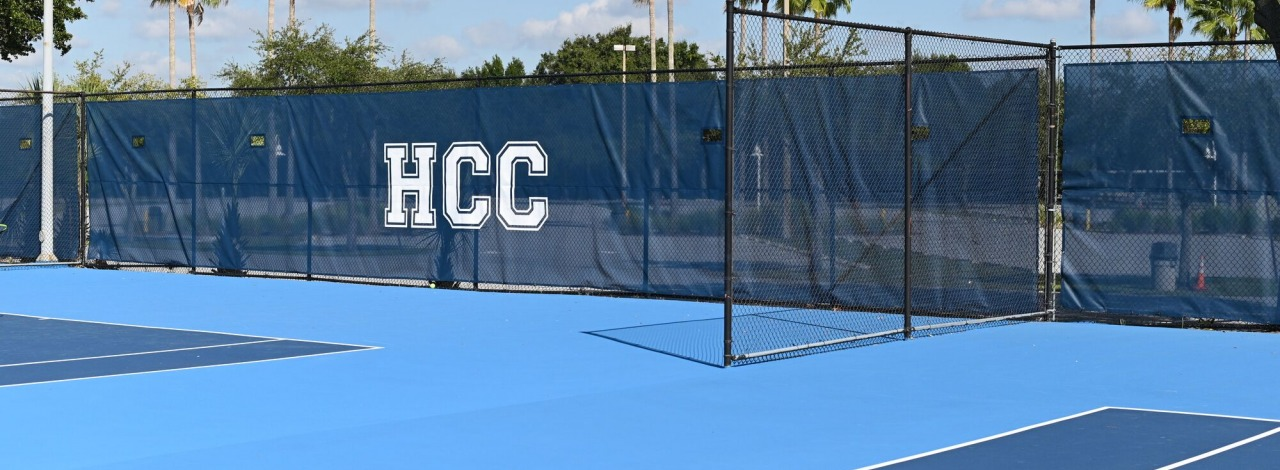 Tennis court with HCC Hawks banners in background