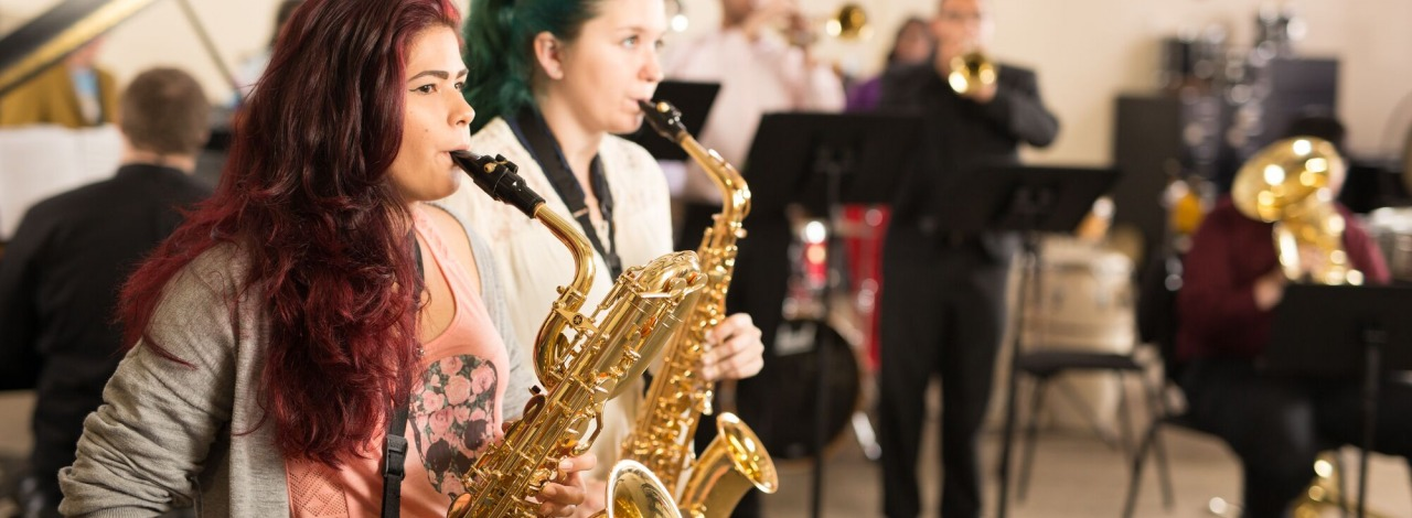 Two female students playing the saxophone with the rest of the HCC Jazz Band behind them