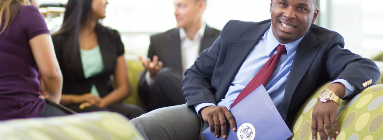 smiling, african american male in a business suit sitting casually on a couch with other business professionals