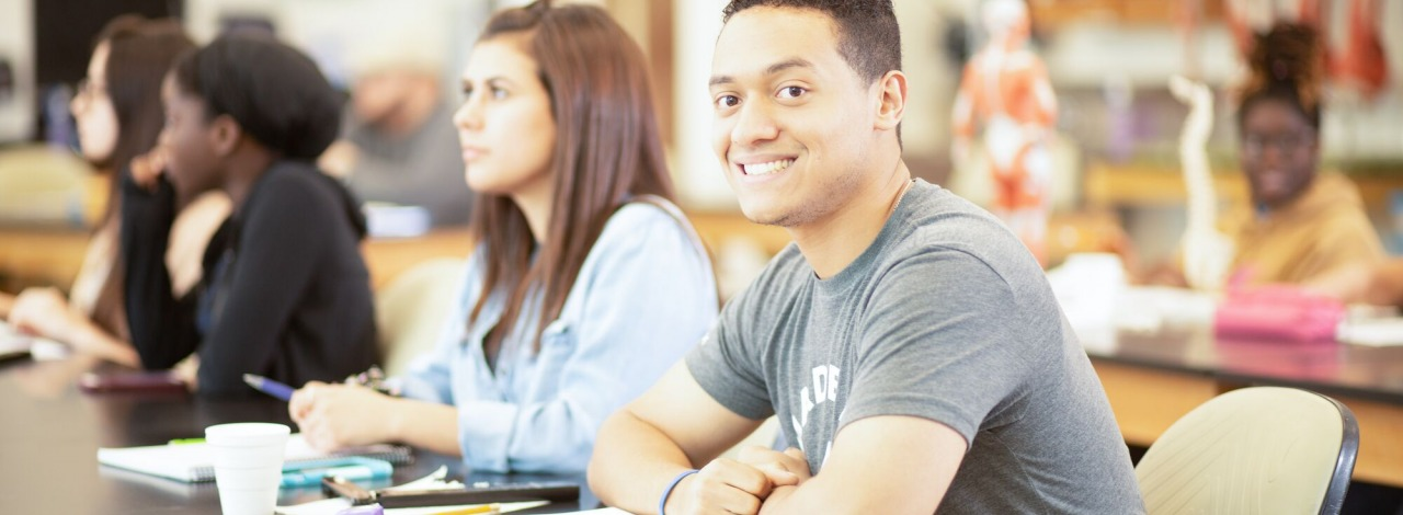 Latino male smiling in a classroom with other students during a lecture