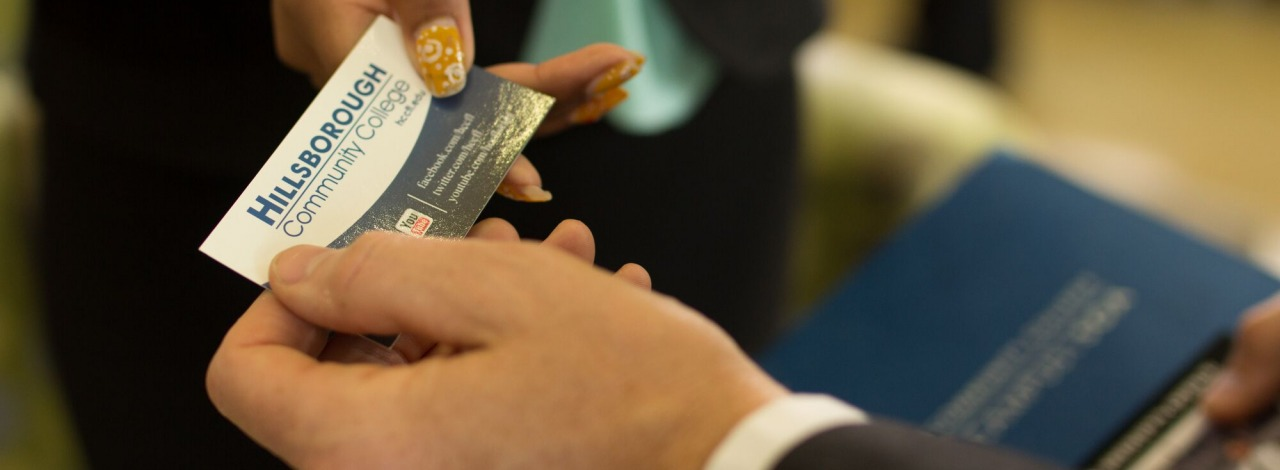 close-up of two people exchanging a business card.