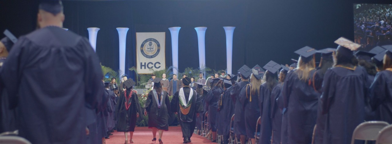 students and faculty dressed in cap and gown at graduation
