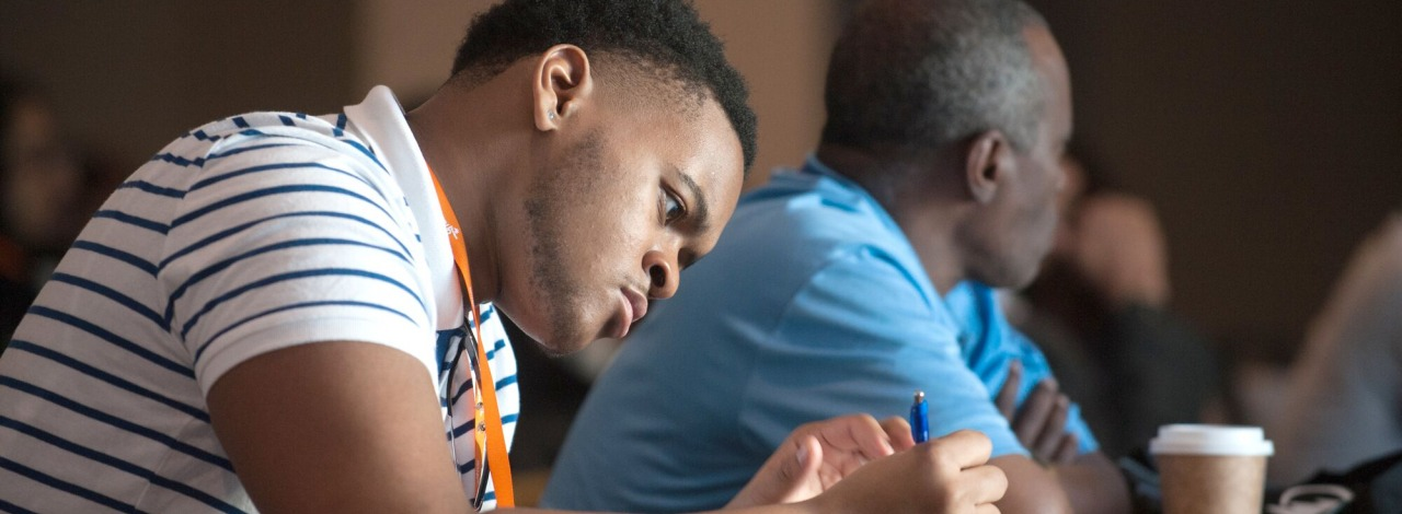 Male student taking notes at BBCB summit