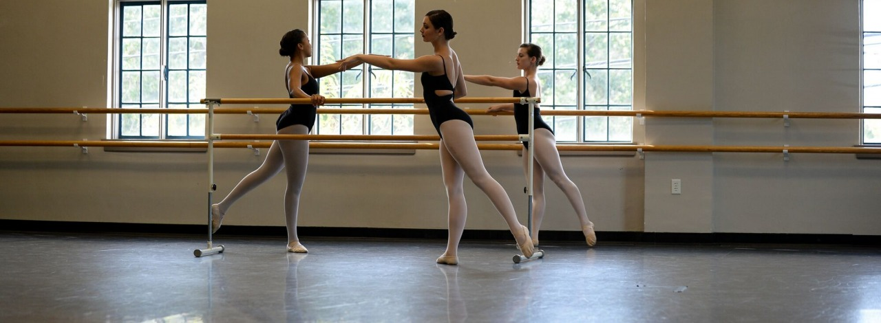 Three students practicing ballet barre