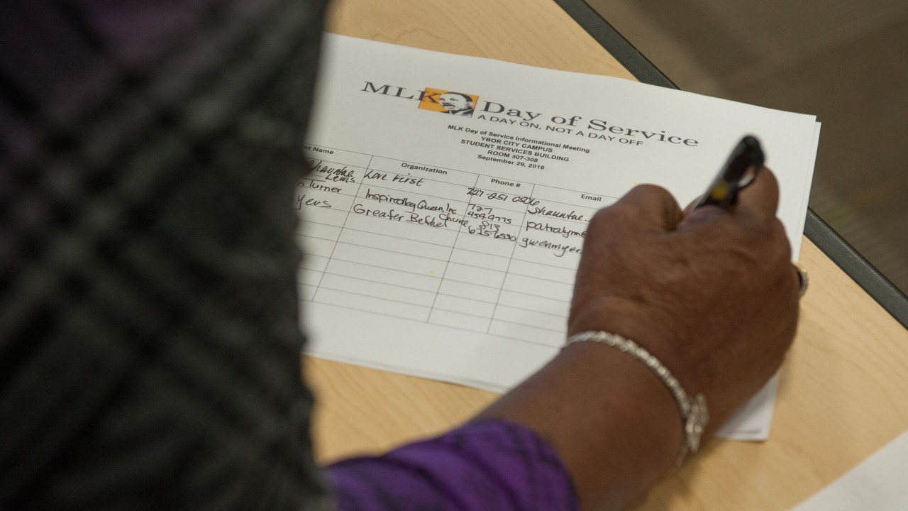 Person's hand filling out a sign-in sheet for MLK Day of Service informational meeting