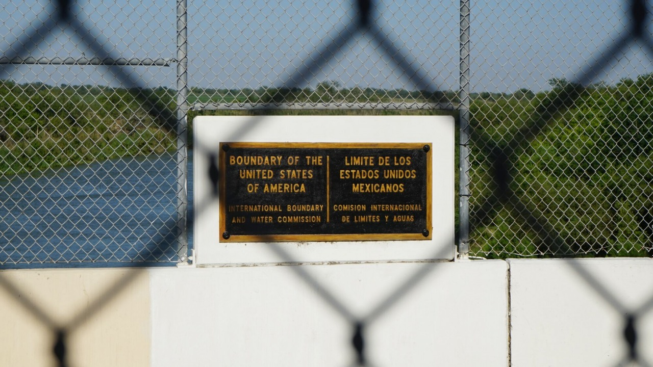 "A chainlink fence with a sign that reads ""boundary of the United States of America"" seen through another chainlink fence"